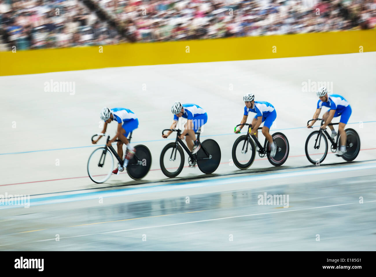 Track cycling team riding around velodrome - Stock Image