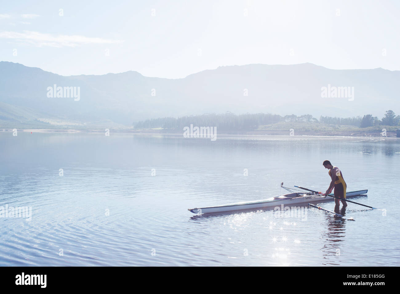 Man placing rowing scull in lake - Stock Image