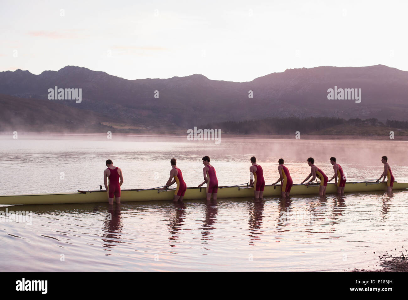 Rowing crew placing scull in lake at dawn - Stock Image