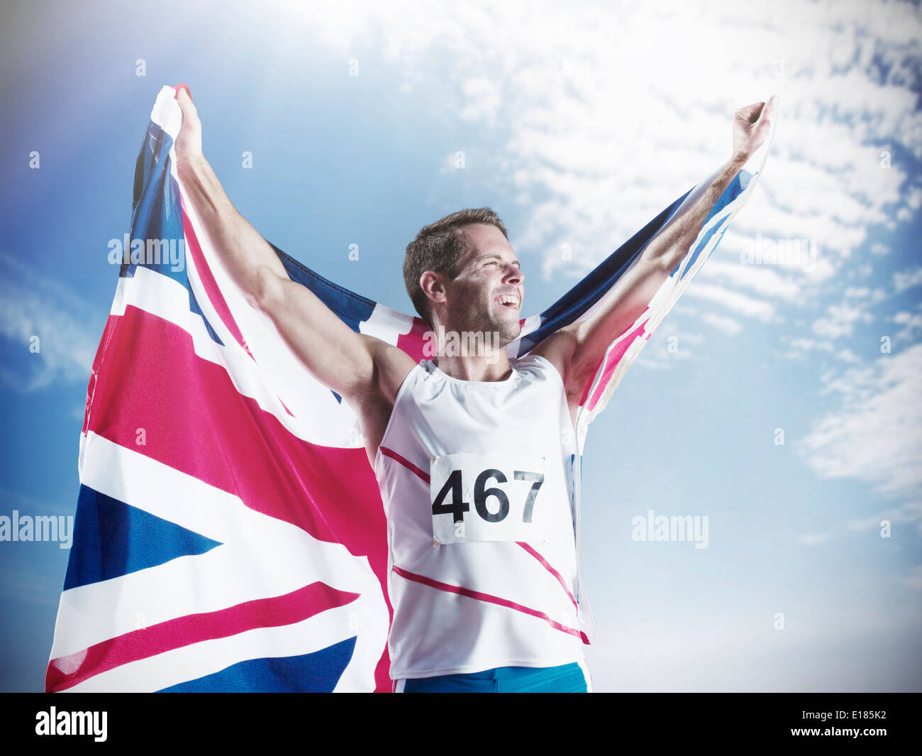 Track and field athlete holding British flag and celebrating Stock Photo