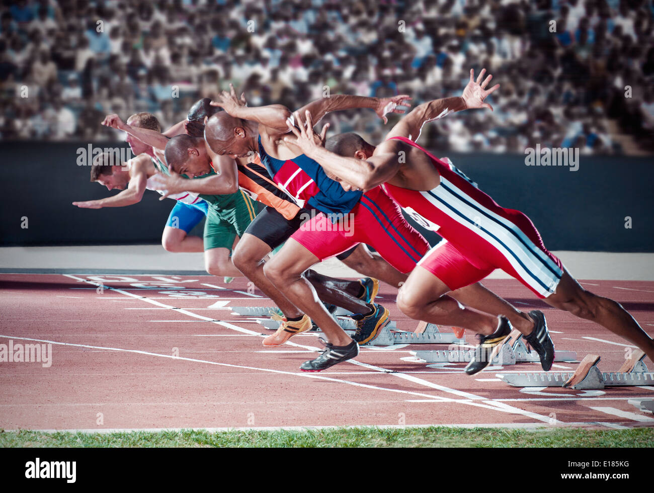 Runners taking off from starting blocks on track - Stock Image