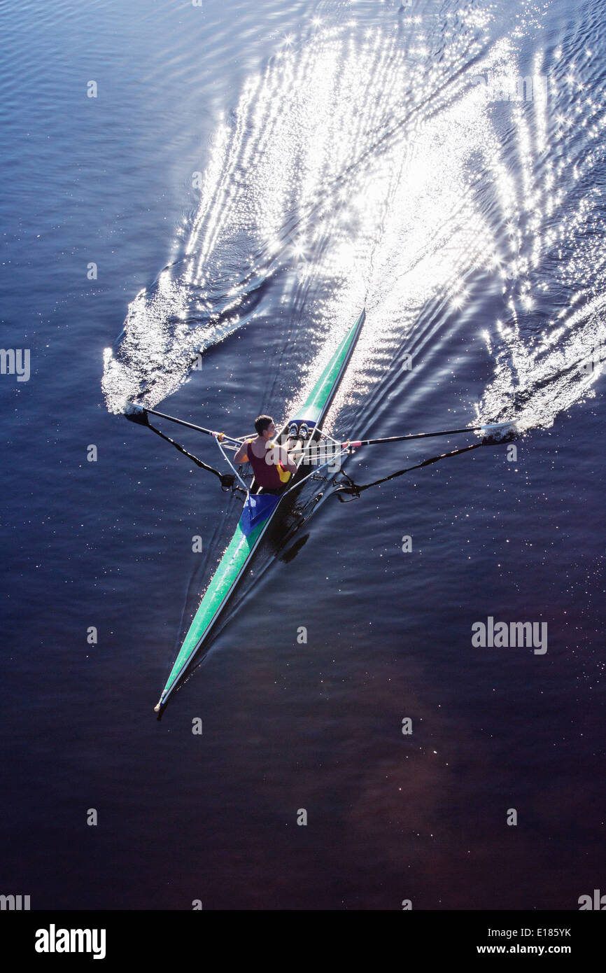 Man rowing scull on lake - Stock Image