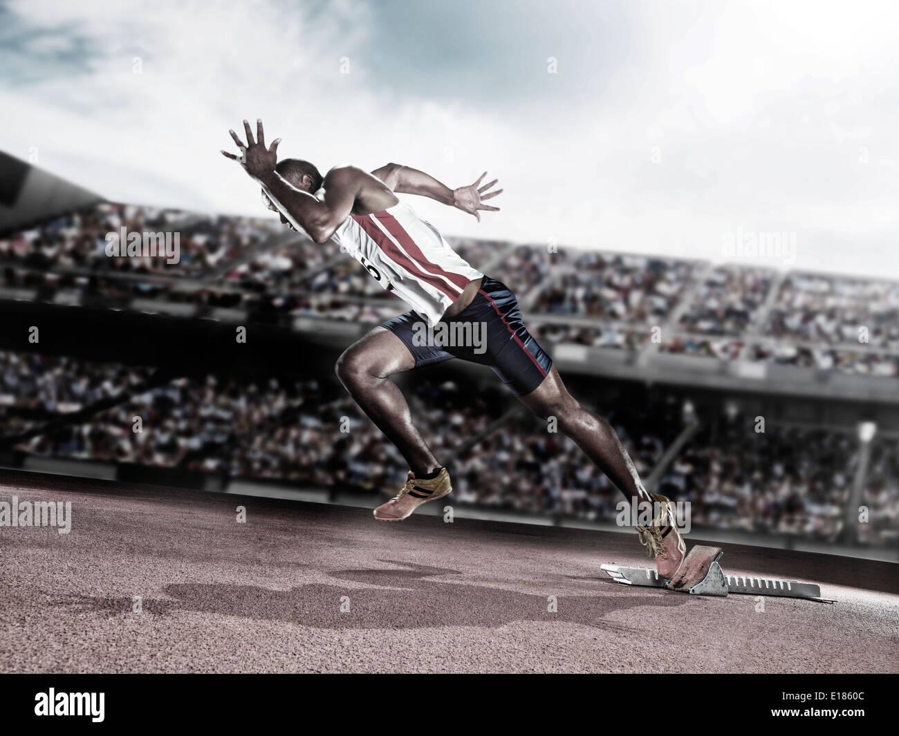 Runner taking off from starting block on track - Stock Image