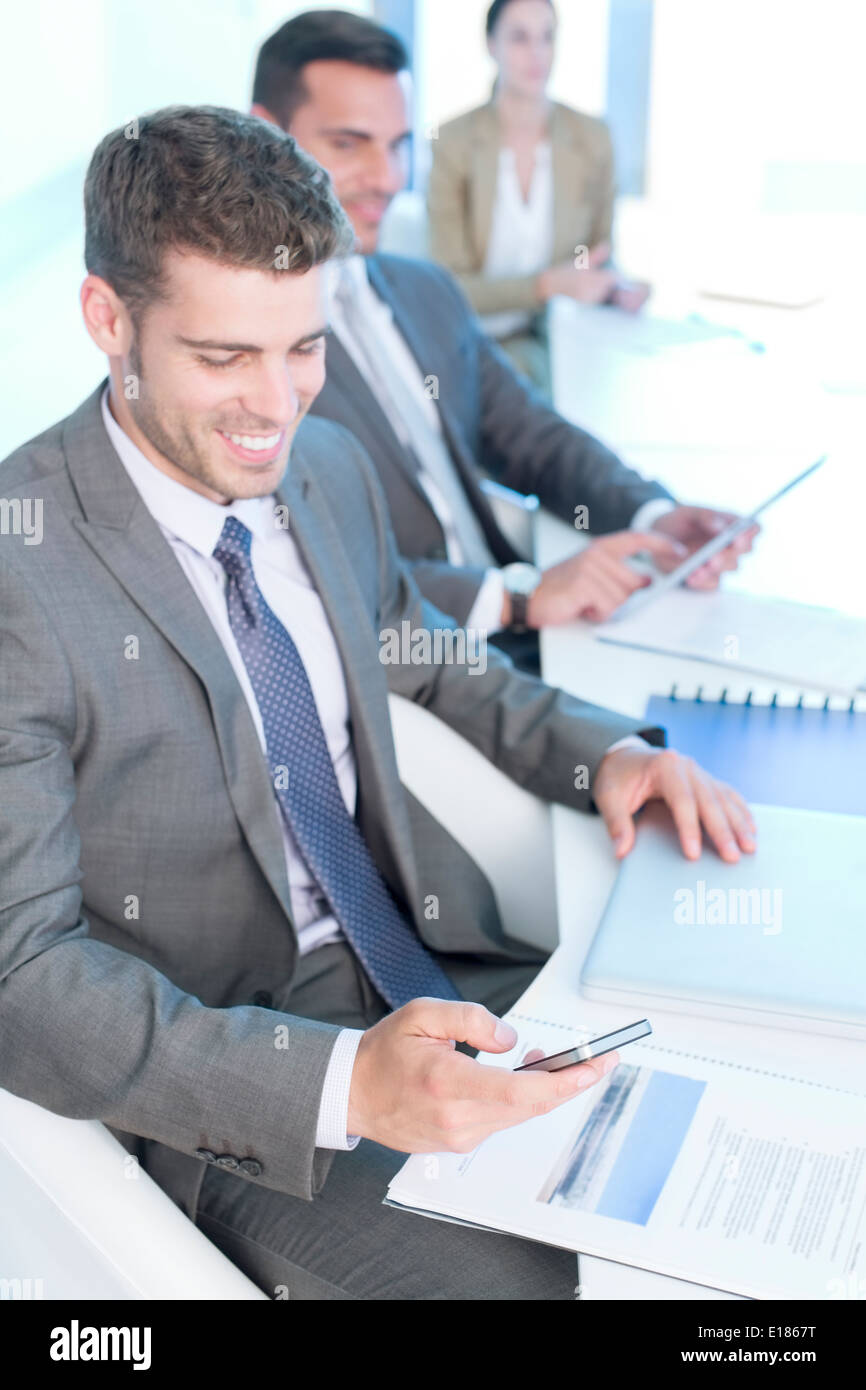 Businessman texting with cell phone in conference room - Stock Image