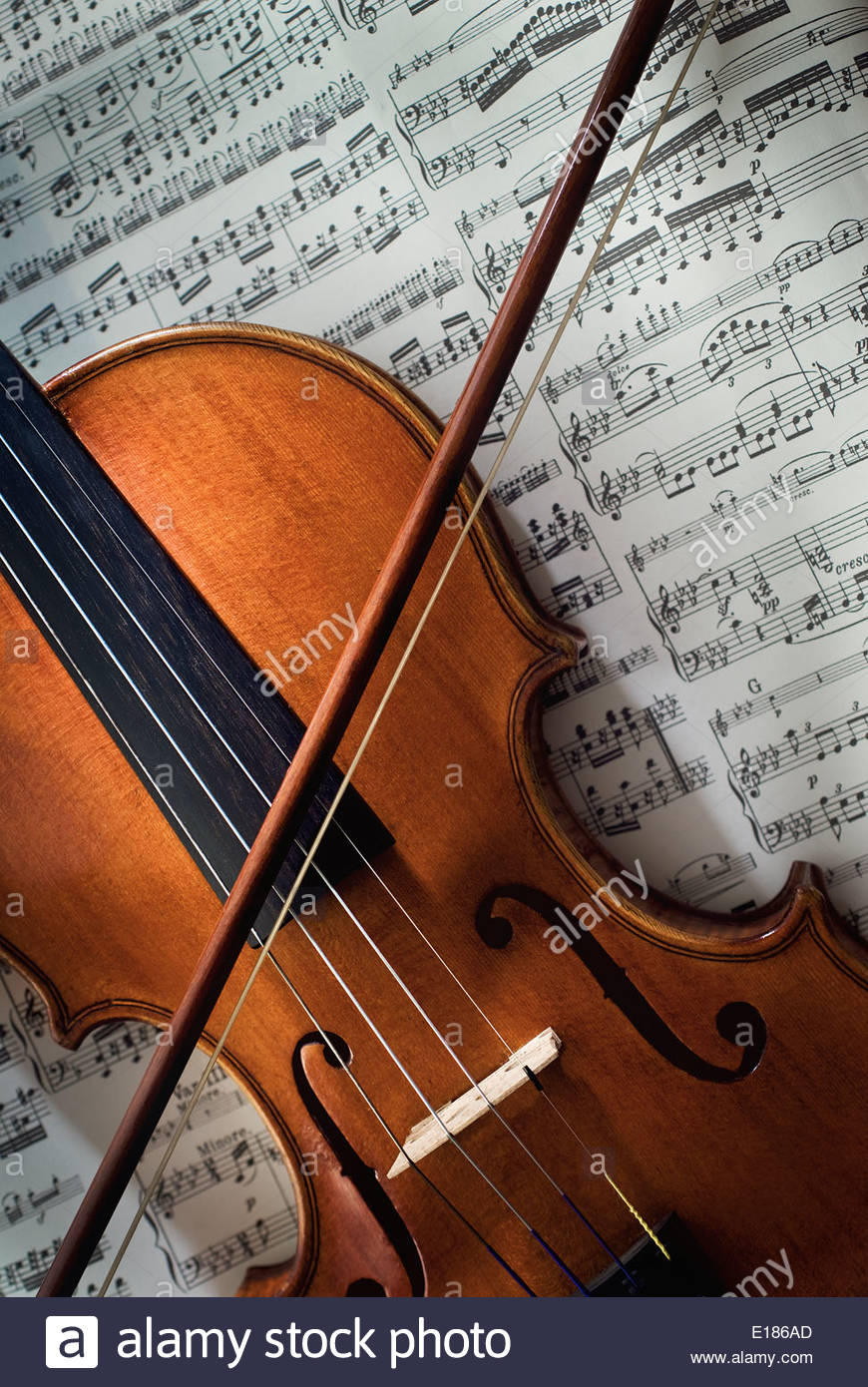 Rare old violin with bow lying on a sheet of music Stock