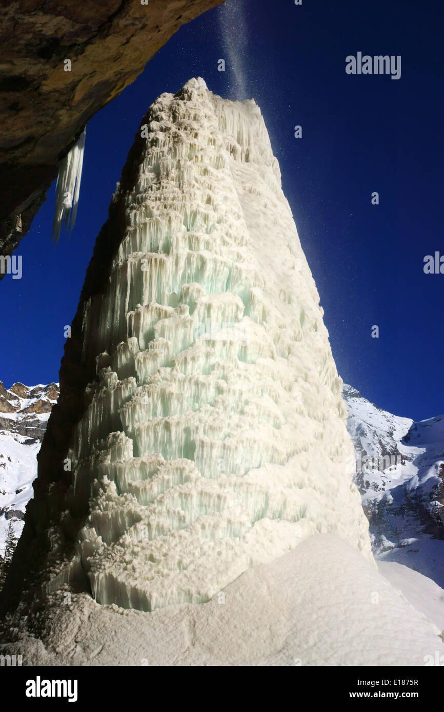 Ice pillar under Waterfall at Oeschinen Lake, Bluemlisalphorn in back. Kandersteg, Bernese alps, Switzerland - Stock Image