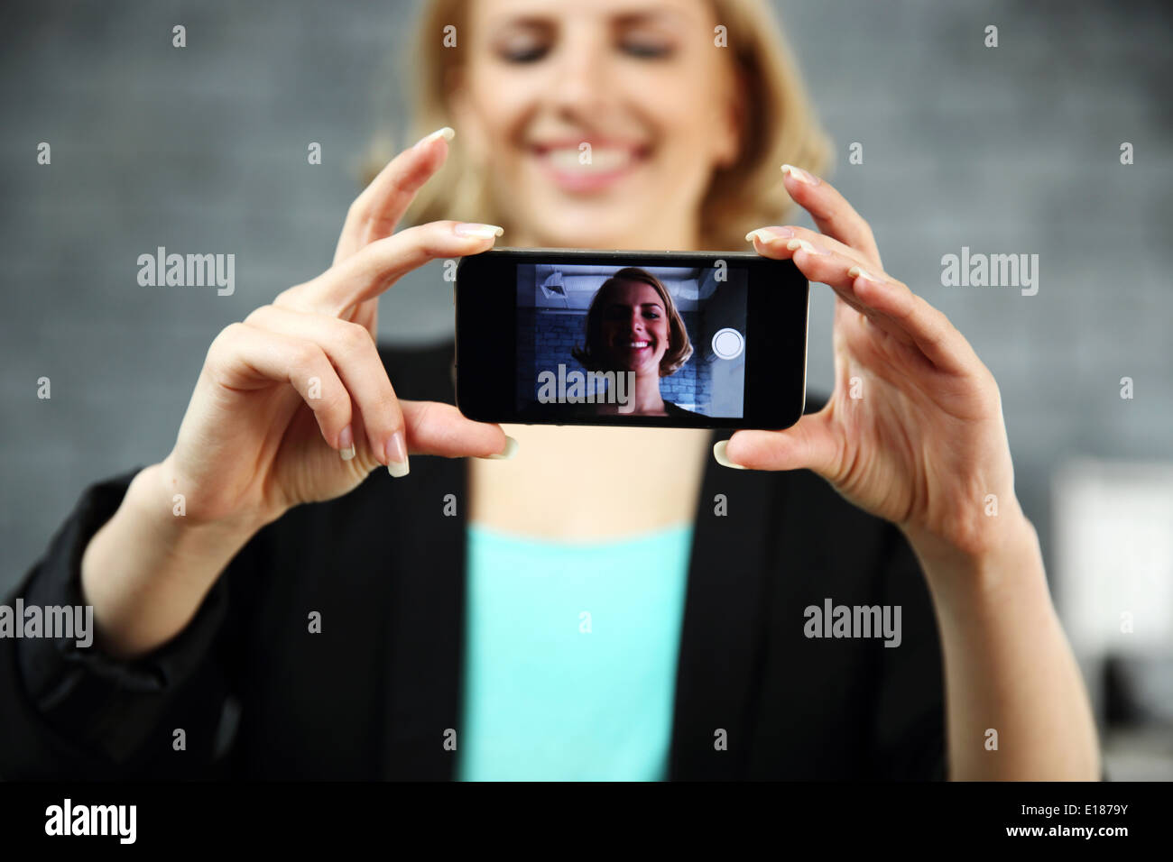 Young smiling woman making a self photo by her smartphone in office. Focus on smartphone - Stock Image
