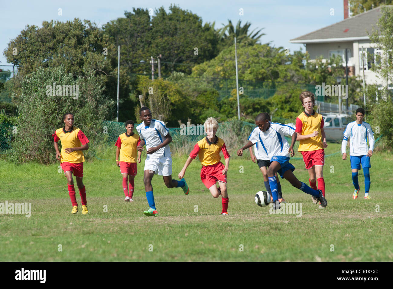 Junior football players chasing the ball, Cape Town, South Africa - Stock Image