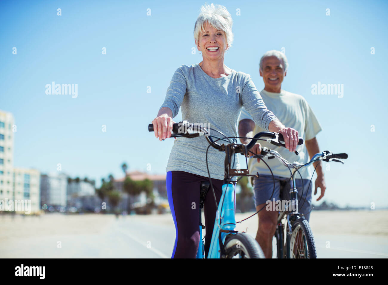 Portrait of senior couple with bicycles on beach boardwalk - Stock Image