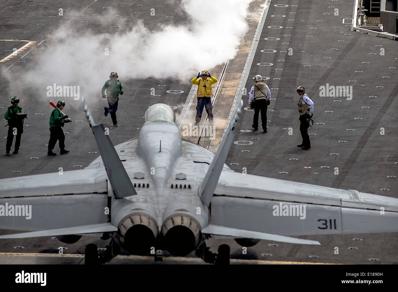 US Navy sailors direct the pilot of an F/A-18E Super Hornet fighter aircraft as it taxis to a catapult in preparation for launch on the flight deck of the Nimitz-class aircraft carrier USS George Washington during operations May 25, 2014 off the coast of Japan. - Stock Image