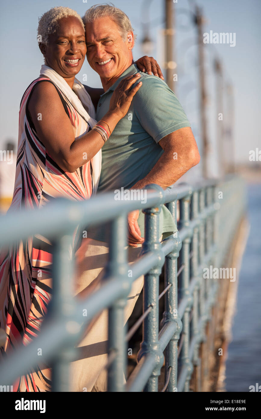 Portrait of smiling senior couple hugging on pier Stock Photo