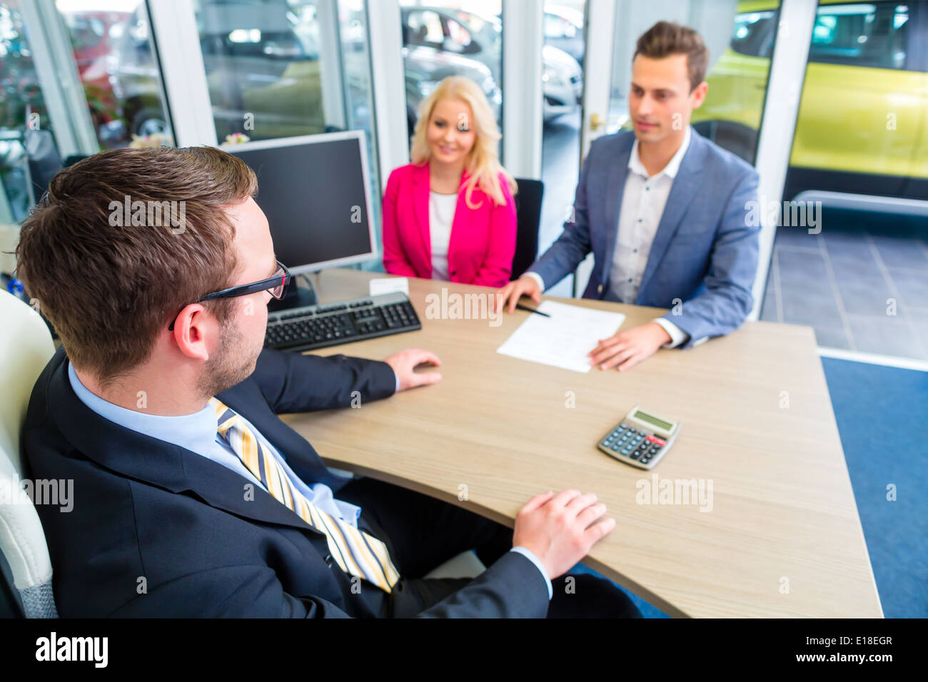 Couple buying car at dealership and negotiating price with salesman - Stock Image