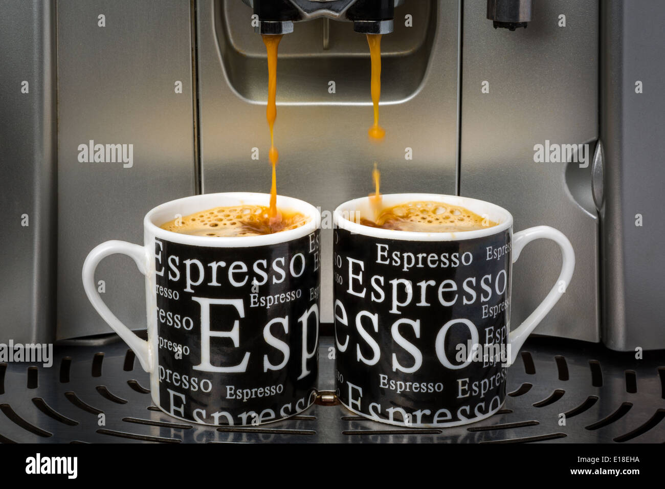 Two espresso cups filled by an automatic espresso machine - Stock Image