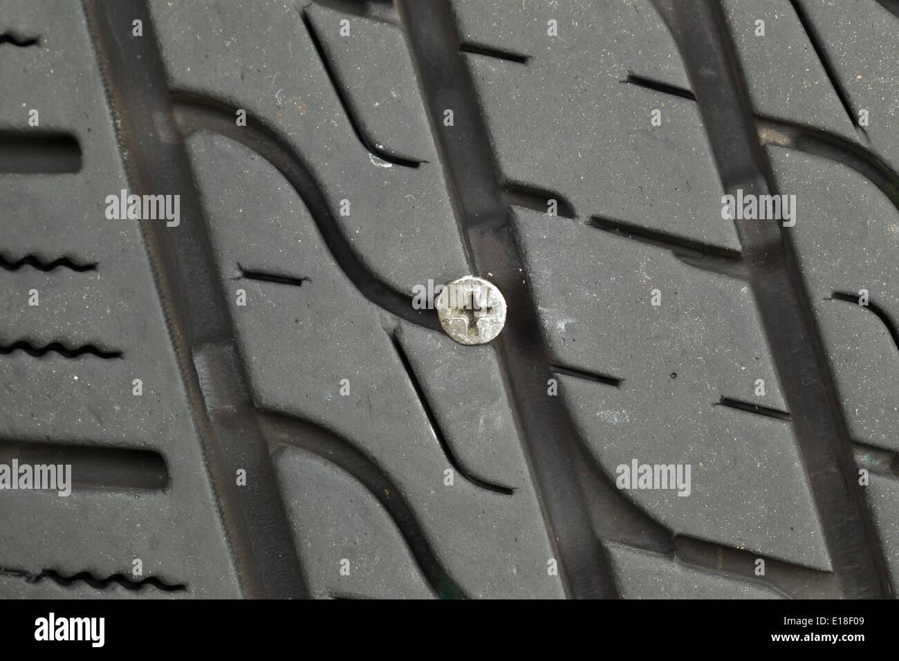 Closeup horizontal photo of wood screw embedded into car tire tread Stock Photo