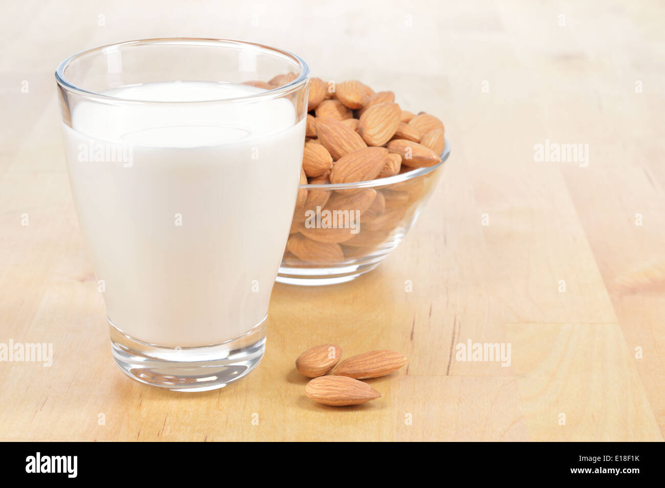 Almond milk as a substitute for dairy milk. Glass of almond milk and bowl of almonds on a wooden table. - Stock Image