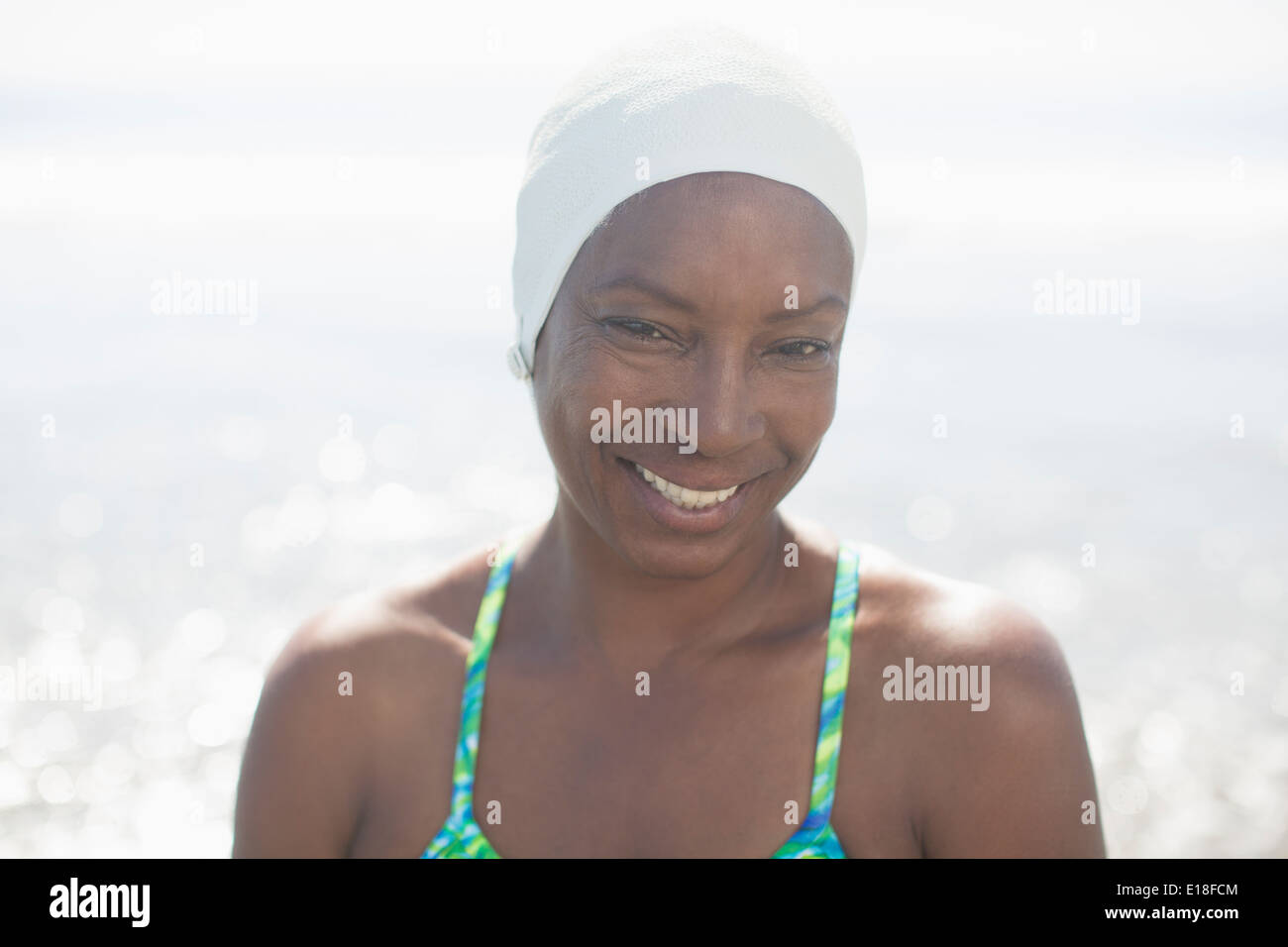 Portrait of smiling woman in swimming cap at beach Stock Photo