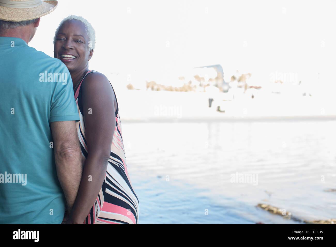 Portrait of smiling senior couple on beach - Stock Image