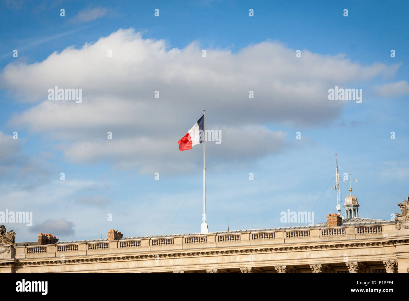 Flag of France fluttering on a pole placed on the top of a vintage building, under a serene blue sky with white clouds - Stock Image