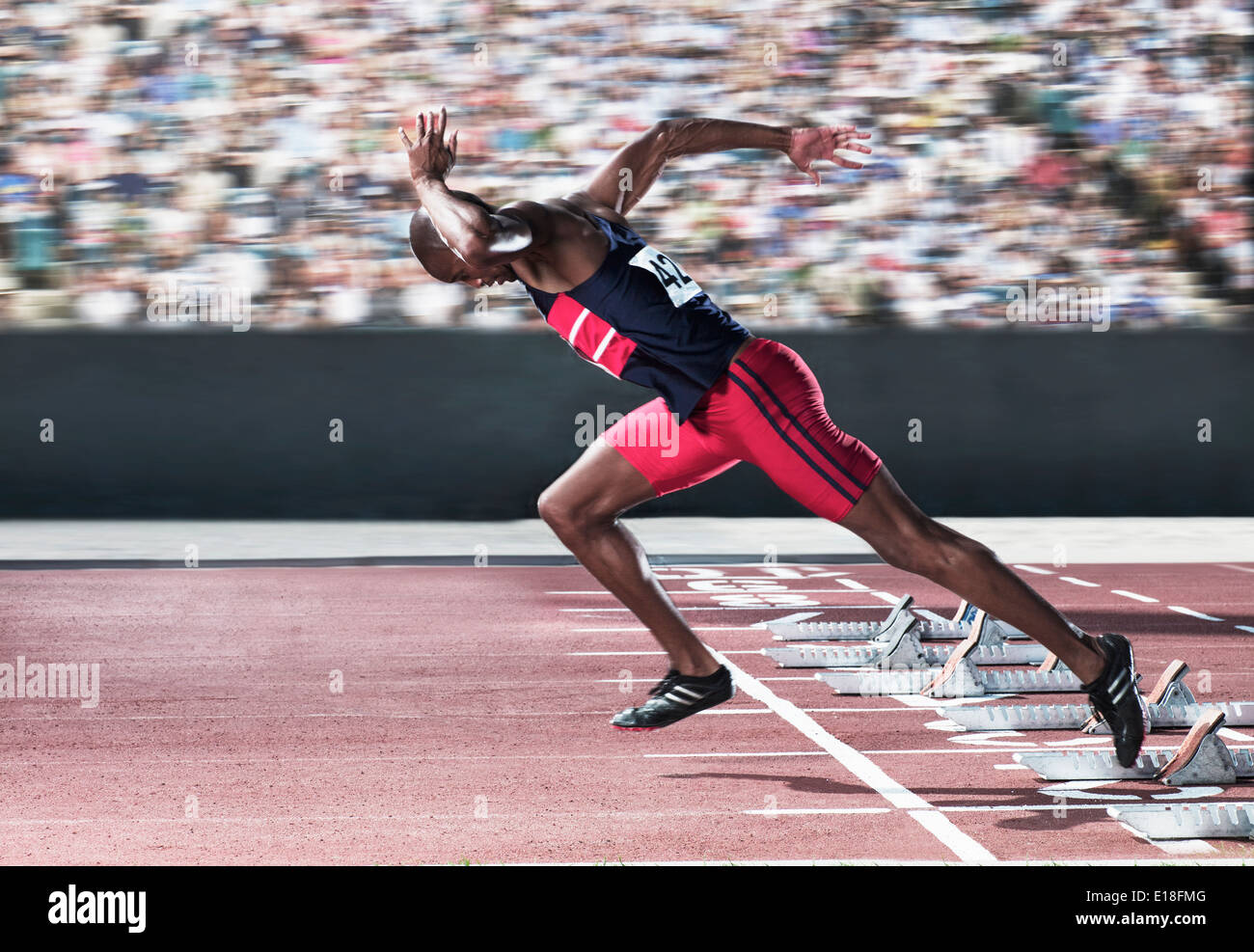 Sprinter taking off from starting block on track - Stock Image