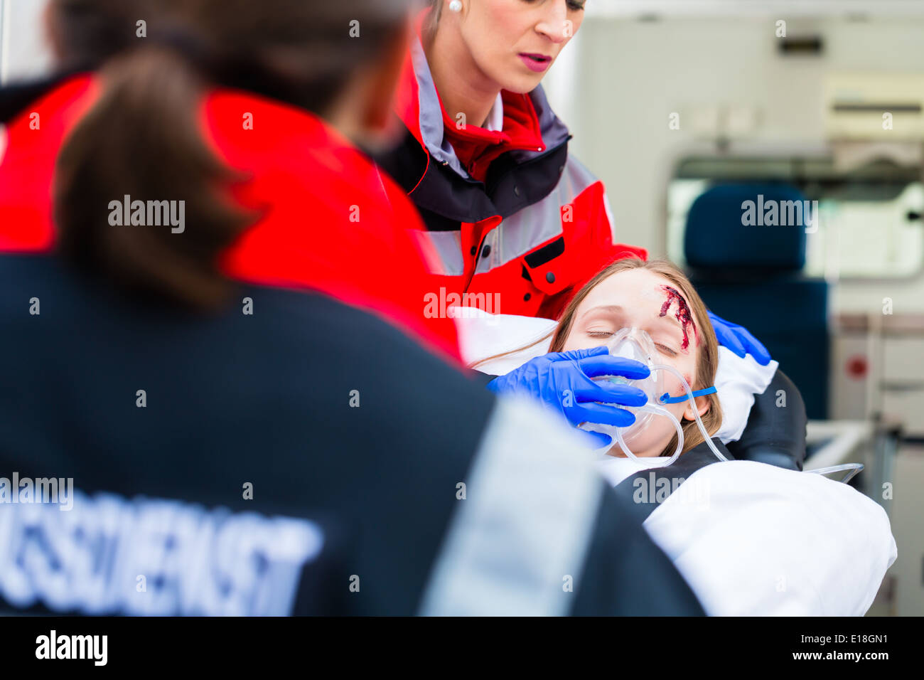 Emergency doctor and nurse or ambulance team transporting accident victim on stretcher Stock Photo