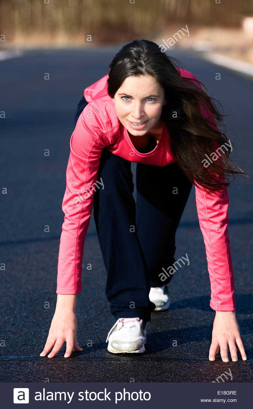Hübsche junge Frau befindet sich in Startposition für einen Sprint - Stock Image