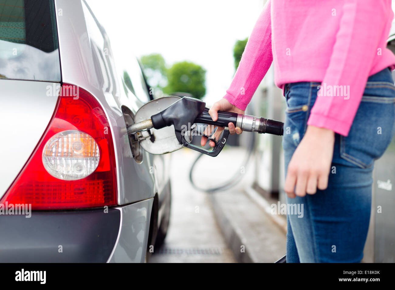 Lady pumping gasoline fuel in car at gas station. - Stock Image