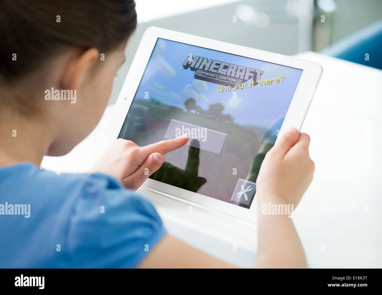 Little girl start playing Minecraft game on brand new Apple iPad Air. Minecraft is very popular game for mobile devices - Stock Image