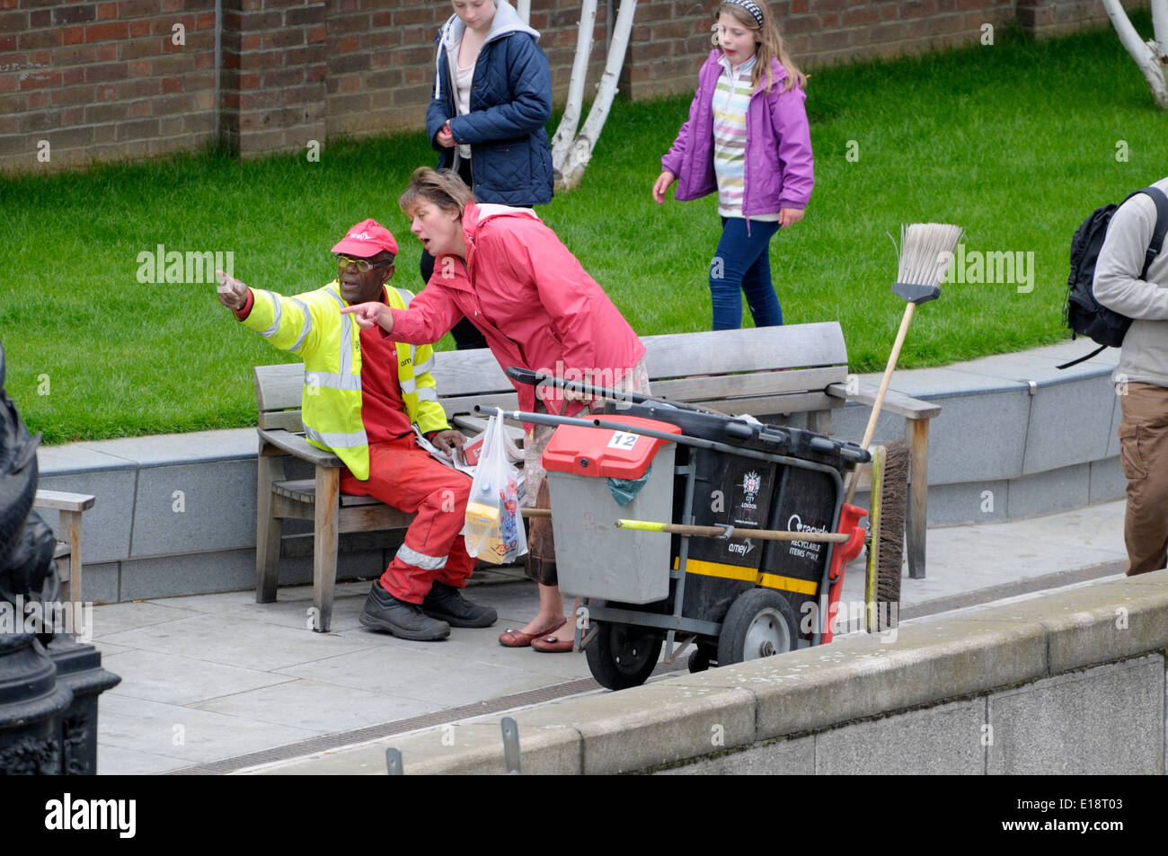 London, England, UK. Road sweeper reading a newspaper on a bench and giving directions to a tourist - Stock Image