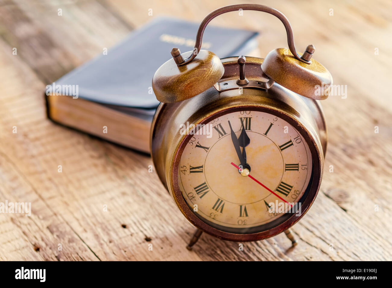 Clock and Bible on wood. Concept of clock showing a few minutes to twelve o'clock. Focus on the clock. - Stock Image