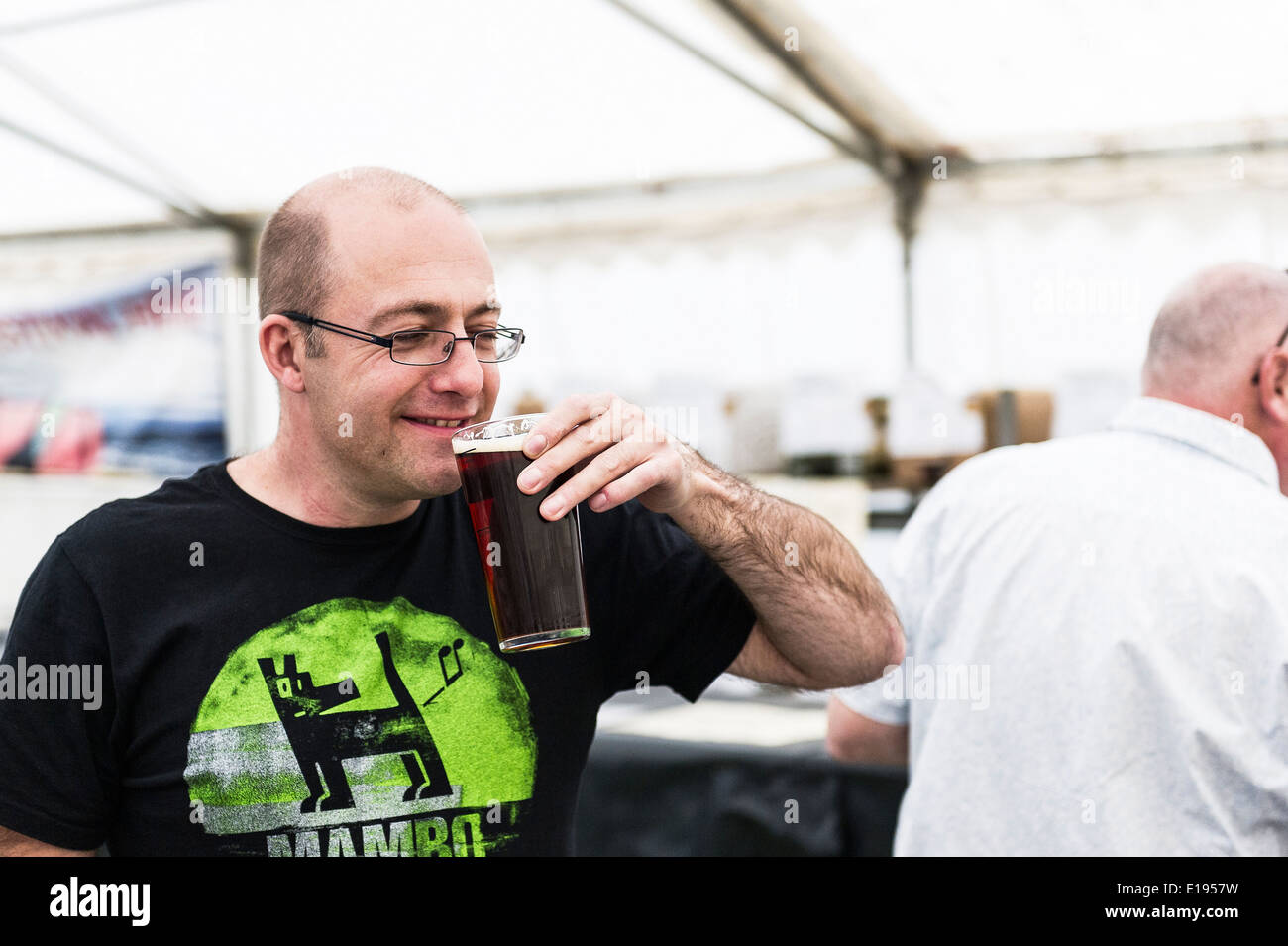 A happy customer tasting his first pint of real ale of the day at the Hoop Beer Festival. - Stock Image