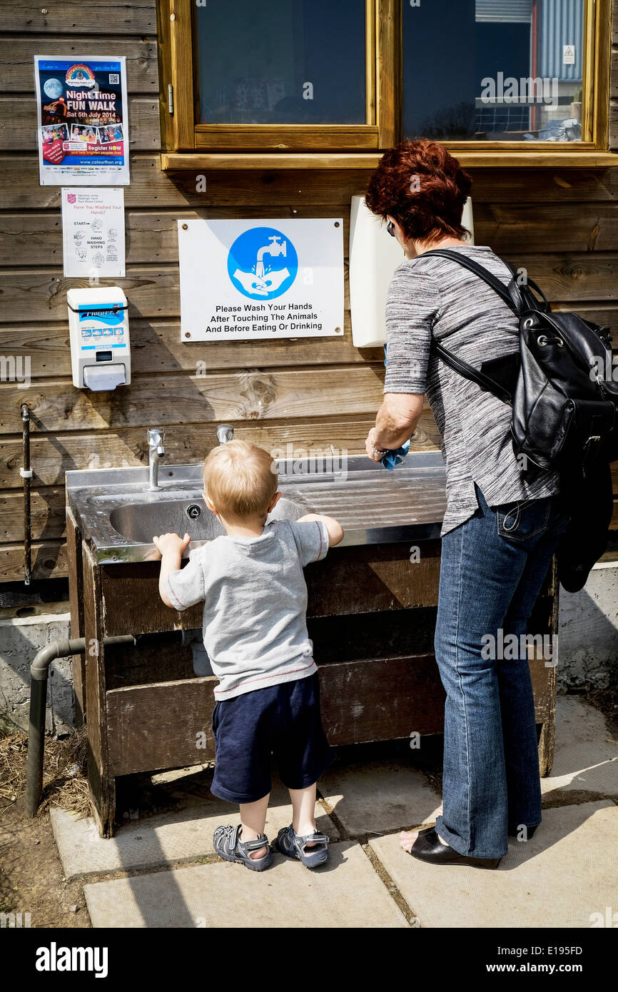 A woman and a child washing their hands at a petting farm. - Stock Image