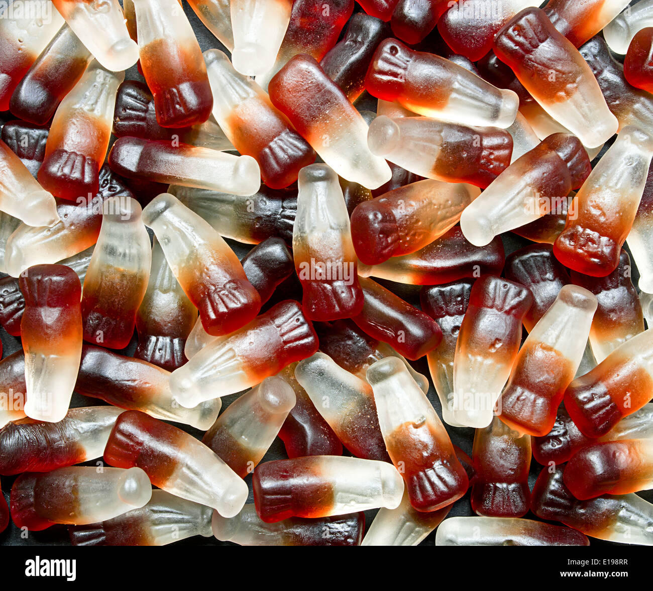 Chewy Cola Bottle background a popular retro sweet also known as Gummy candy at a pick and mix self service market. - Stock Image