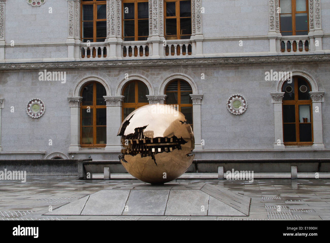 Metal sculpture called 'Sphere within Sphere' by Arnaldo Pomodoro on the grounds of Trinity College Dublin,Ireland - Stock Image