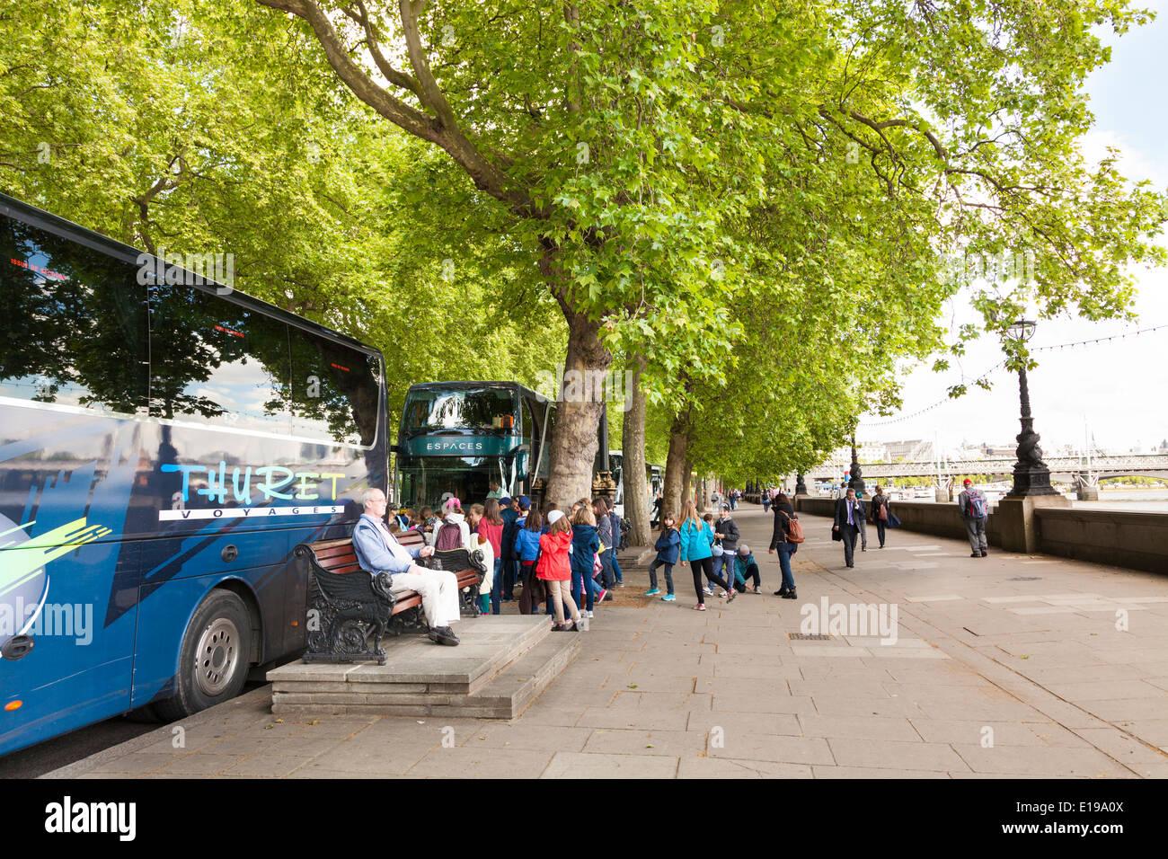 School age children boarding tourists coaches on Victoria Embankment London. - Stock Image