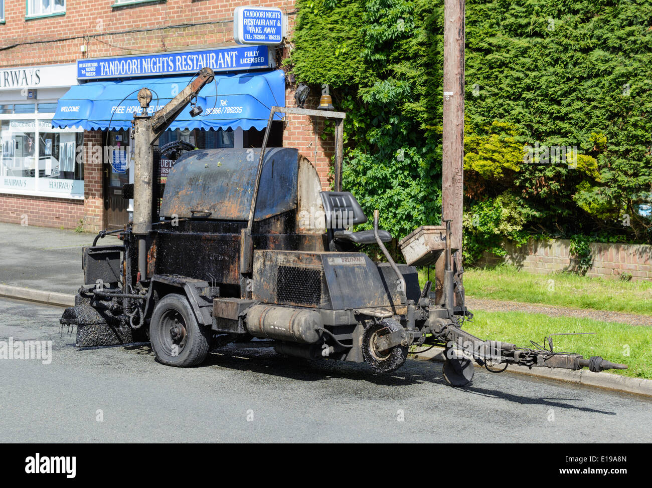Tarmac machine parked at the side of the road. - Stock Image