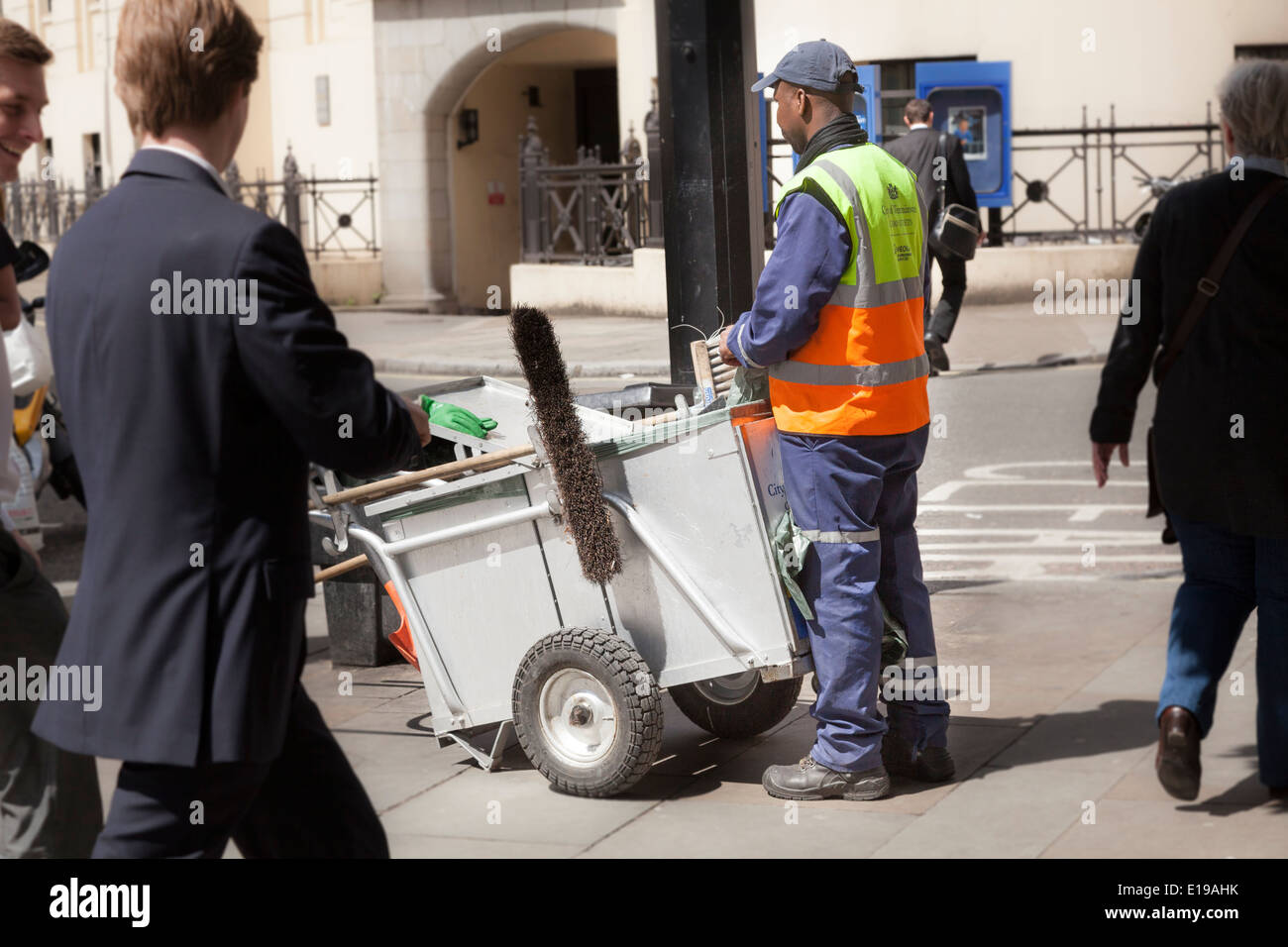 Street cleaner with cart amidst the bustle of a London street. - Stock Image