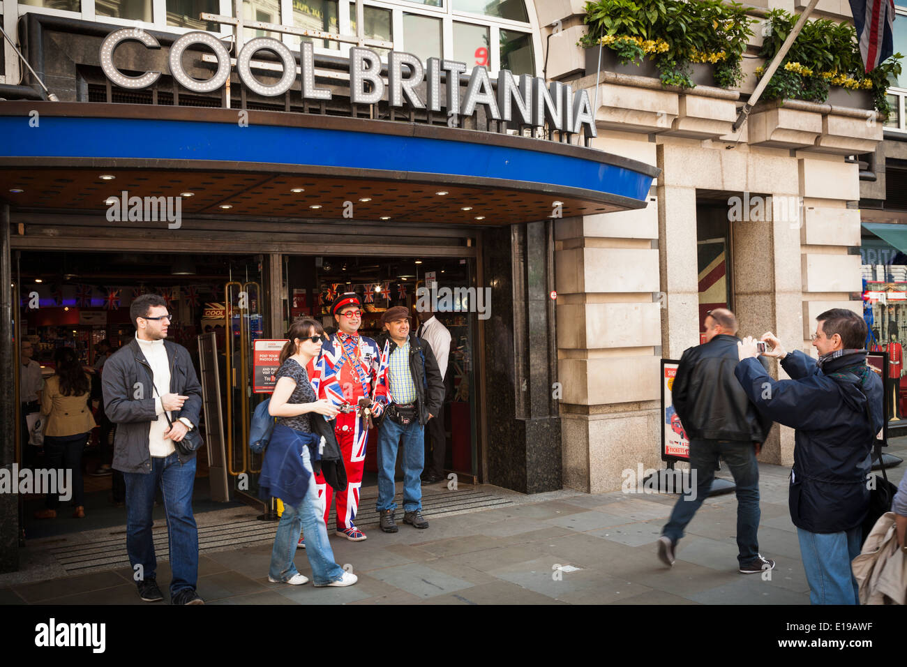 Tourists photographed with the door man at Cool Britannia in Piccadilly London. - Stock Image