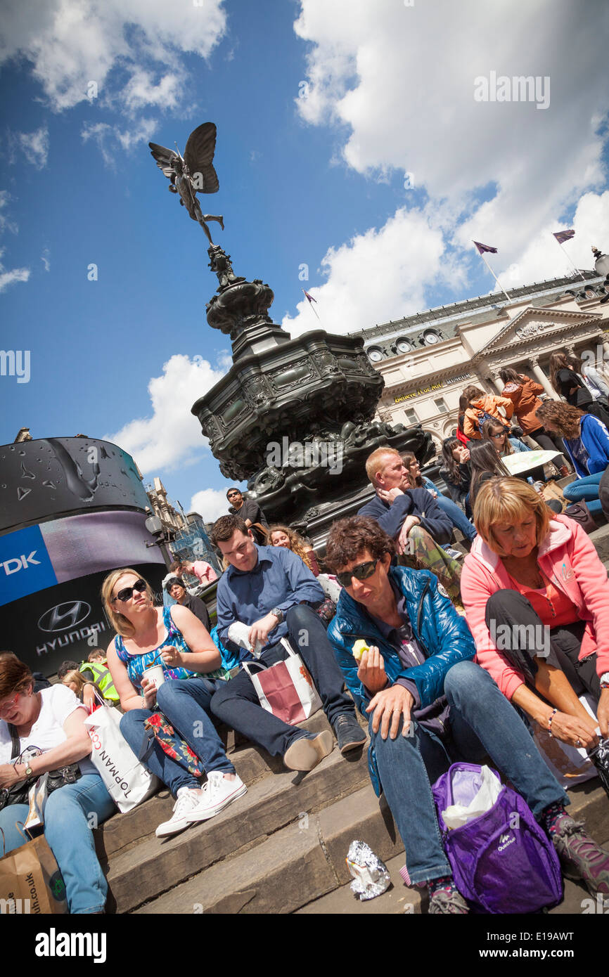 Tourists gather to sit around Eros statue in Piccadilly Circus London - Stock Image