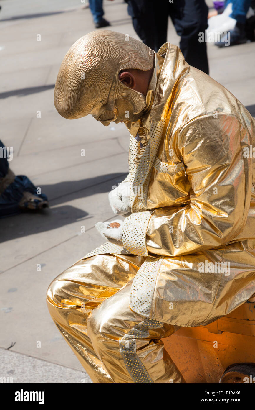 Living statue of a gold elvis in Piccadilly Circus London counting his takings. - Stock Image