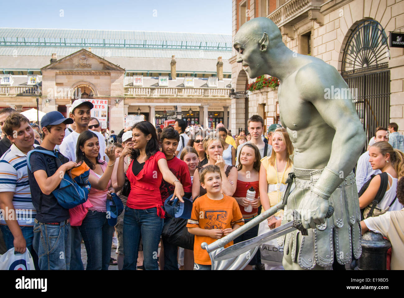 Mime artist Duncan Meadows as a giant green human statue performing for tourists at Covent Garden, London, England, UK - Stock Image