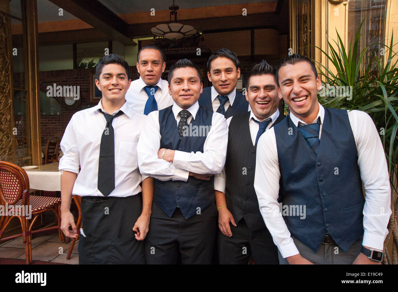 Group of Hispanic waiters posing for a photo outside restaurant on Mulberry Street in Little Italy, New York City, USA - Stock Image