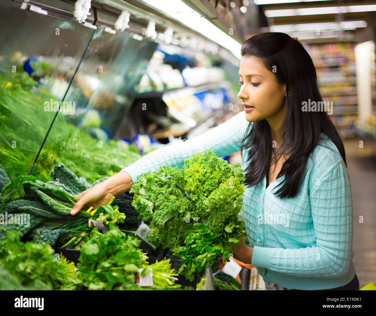 Closeup portrait, beautiful, pretty young woman in sweater picking up, choosing green leafy vegetables in grocery store - Stock Image