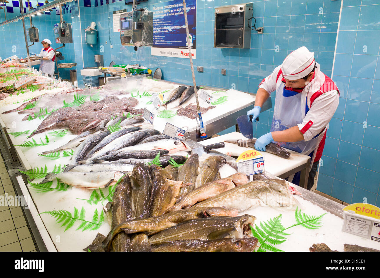 Fishmonger cutting fresh fish at Alcampo supermarket, Madrid, Spain - Stock Image