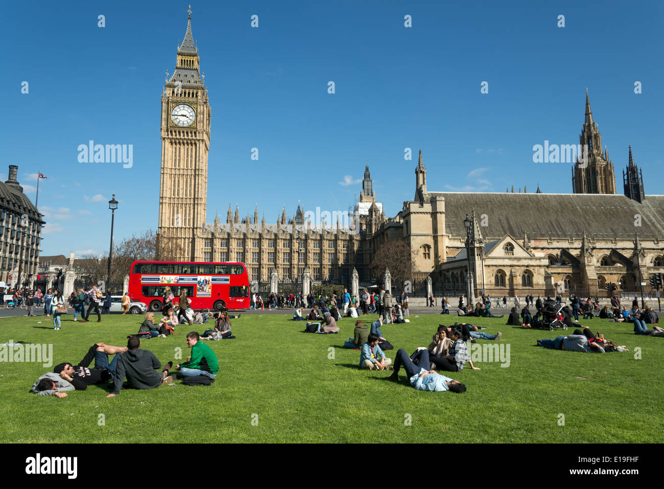 People relaxing in Parliament Square, London, England, UK - Stock Image
