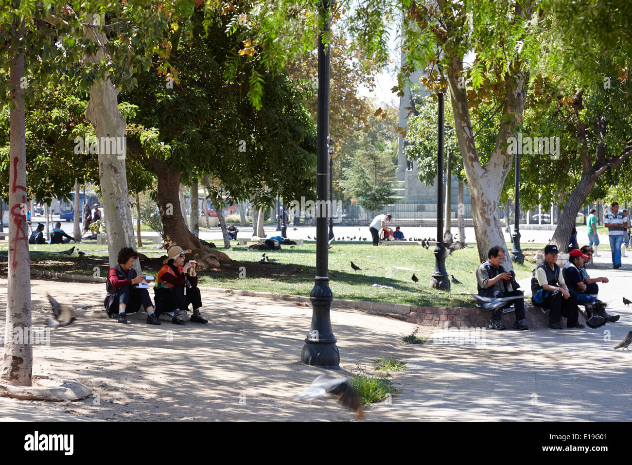 asian tourists resting under shady trees in a park in Santiago Chile - Stock Image