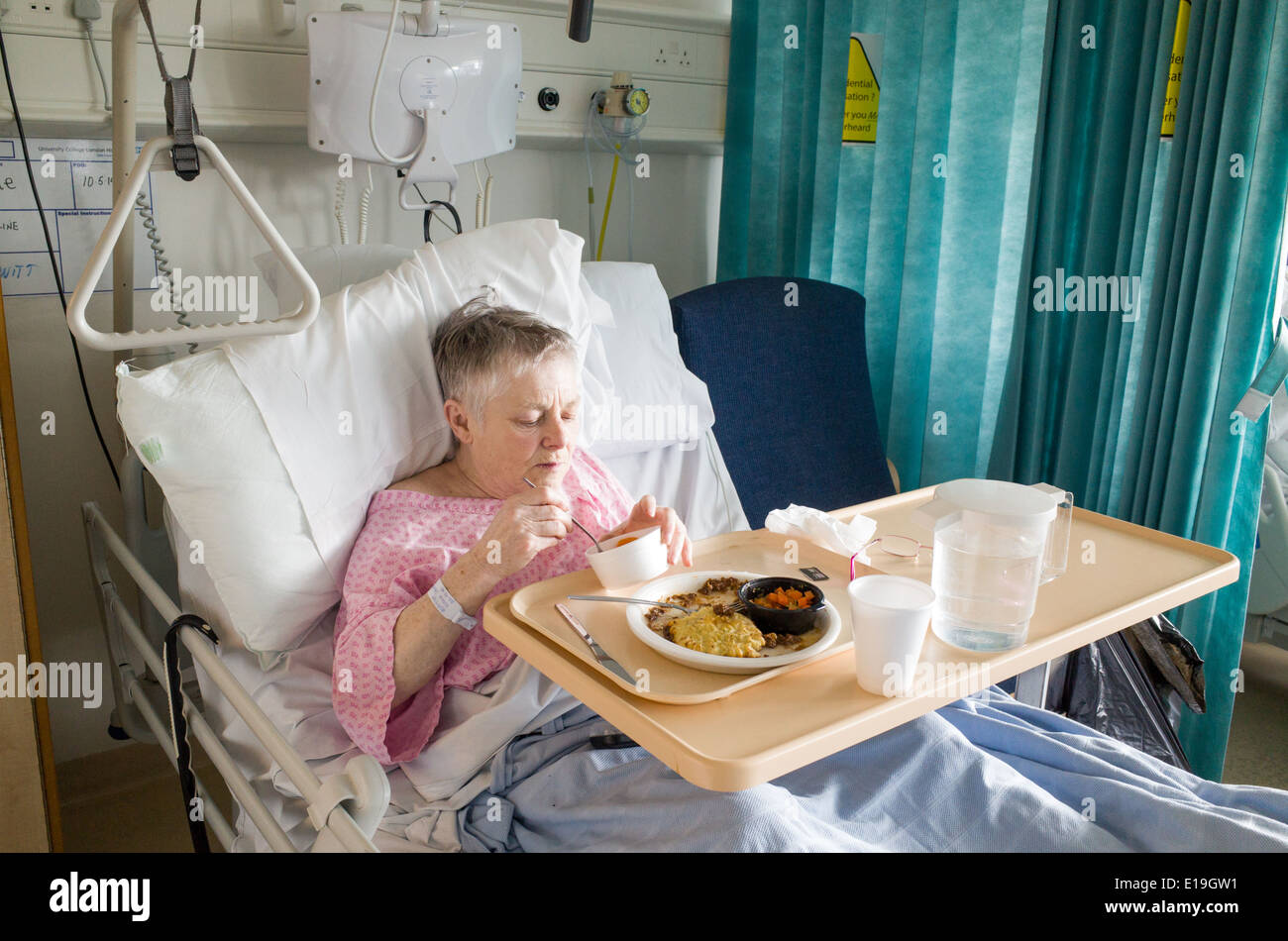 Elderly patient in University College Hospital eating hospital food, London, England, UK - Stock Image