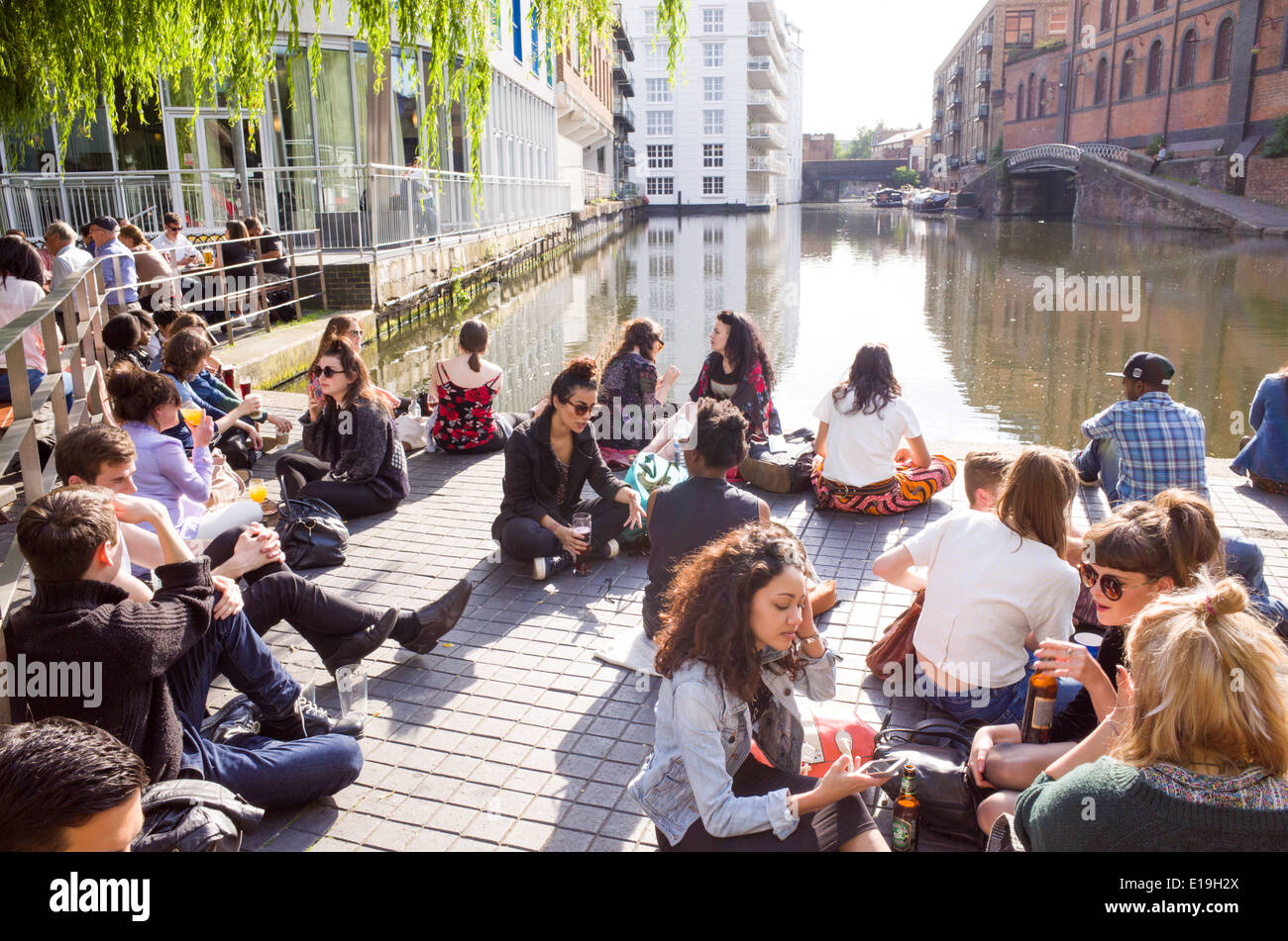 Young people relaxing beside the Regent's Canal in Camden Town, London, England, UK - Stock Image