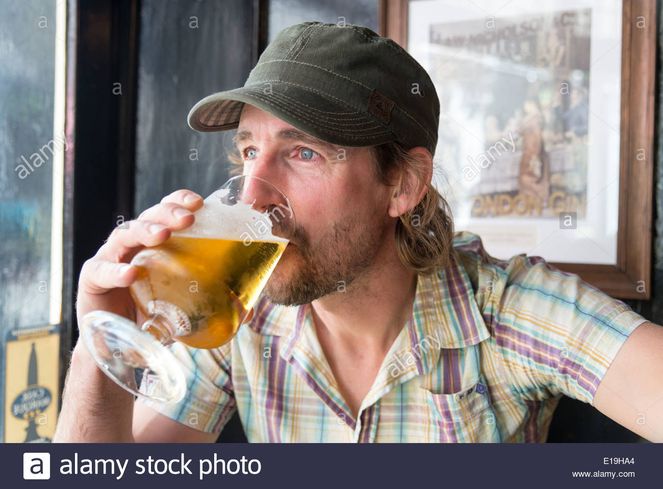 Man drinking pint of lager in pub, England, UK - Stock Image