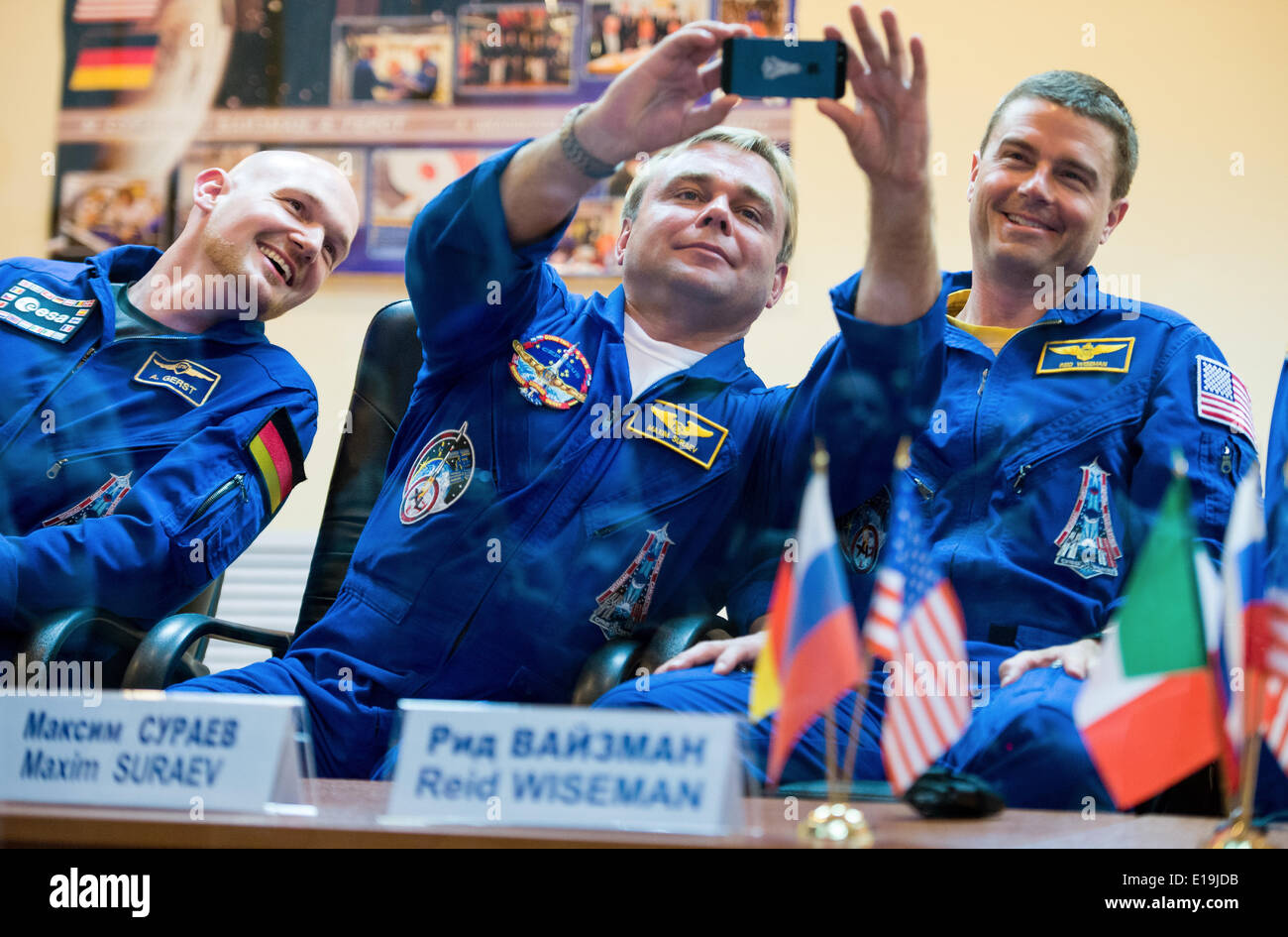 ISS Expedition Expedition 40 Soyuz Commander Maxim Suraev of the Russian Federal Space Agency, Roscosmos, center, takes a picture with his cell phone during a press conference as Alexander Gerst of the European Space Agency , Soyuz Commander Max Suraev of Roscosmos and Flight Engineer Reid Wiseman of NASA look on May 27, 2014 in Baikonur, Kazakhstan. The crew will launch on May 29 in the Soyuz TMA-13M spacecraft from Baikonur for a 5 ½ month mission on the International Space Station. - Stock Image