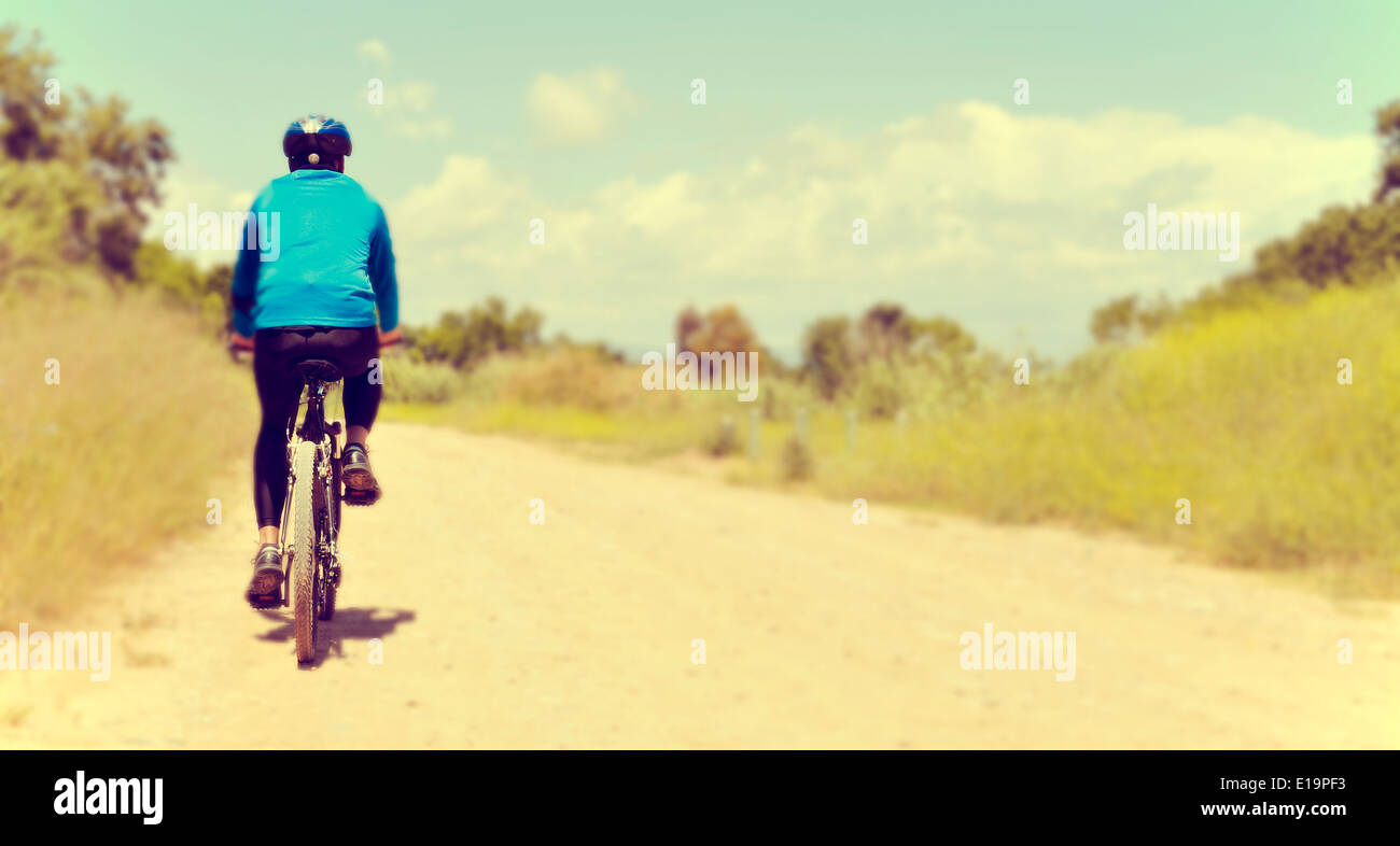 a young man riding a mountain bike on a dirt road - Stock Image